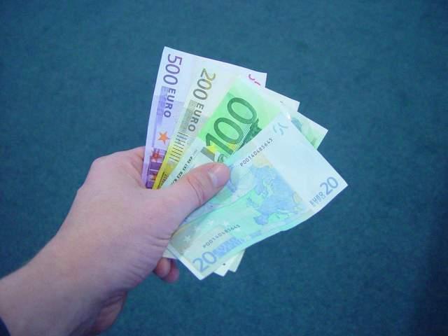 ruce podávající někomu plnou hrst bankovek